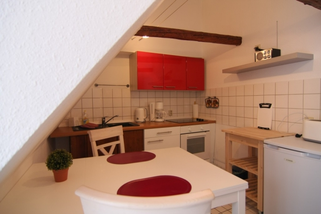 Küche mit Tisch, Stuhl, Küchenschränke, Herd und Beistelltisch