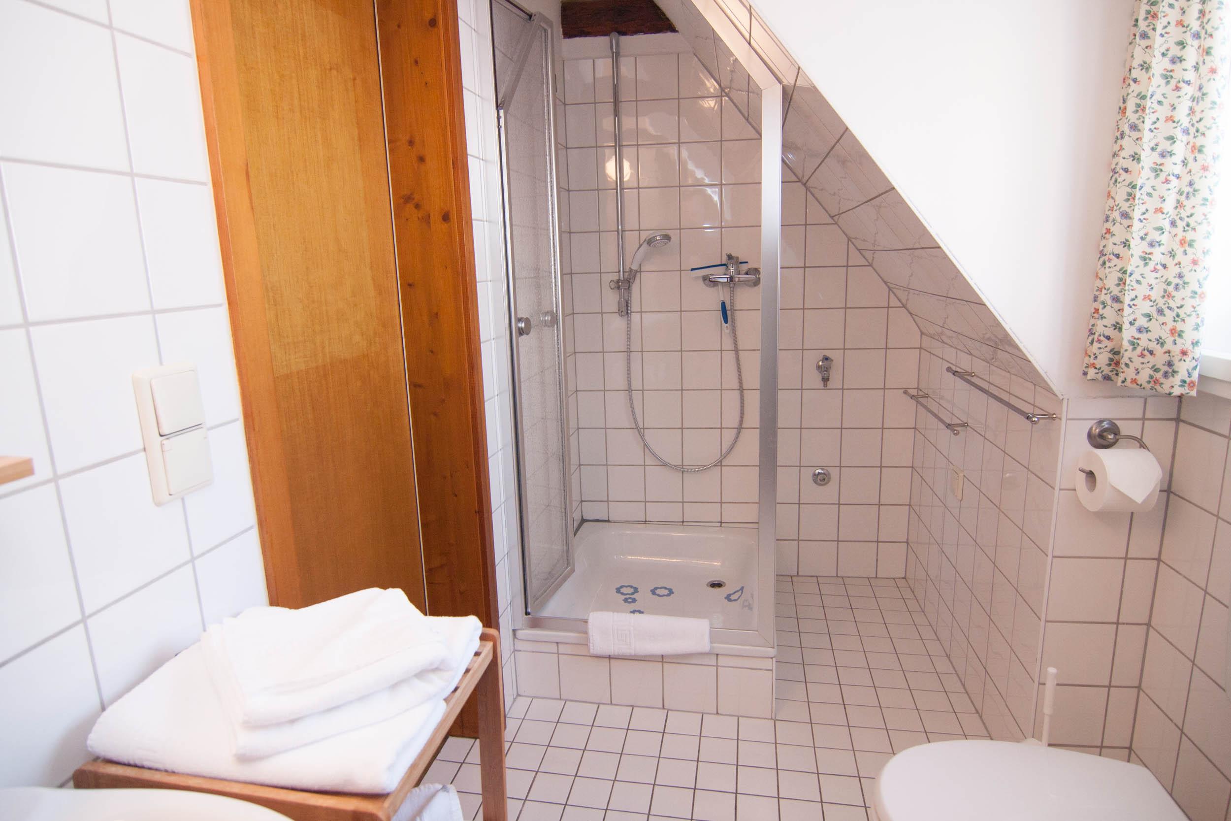 Bad mit Dusche und Handtuchregal