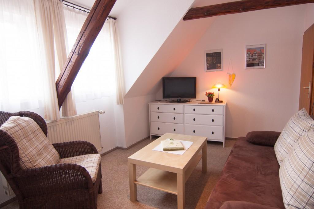 Wohnzimmer mit Fernseher, Sofa, Sofatisch und Sessel
