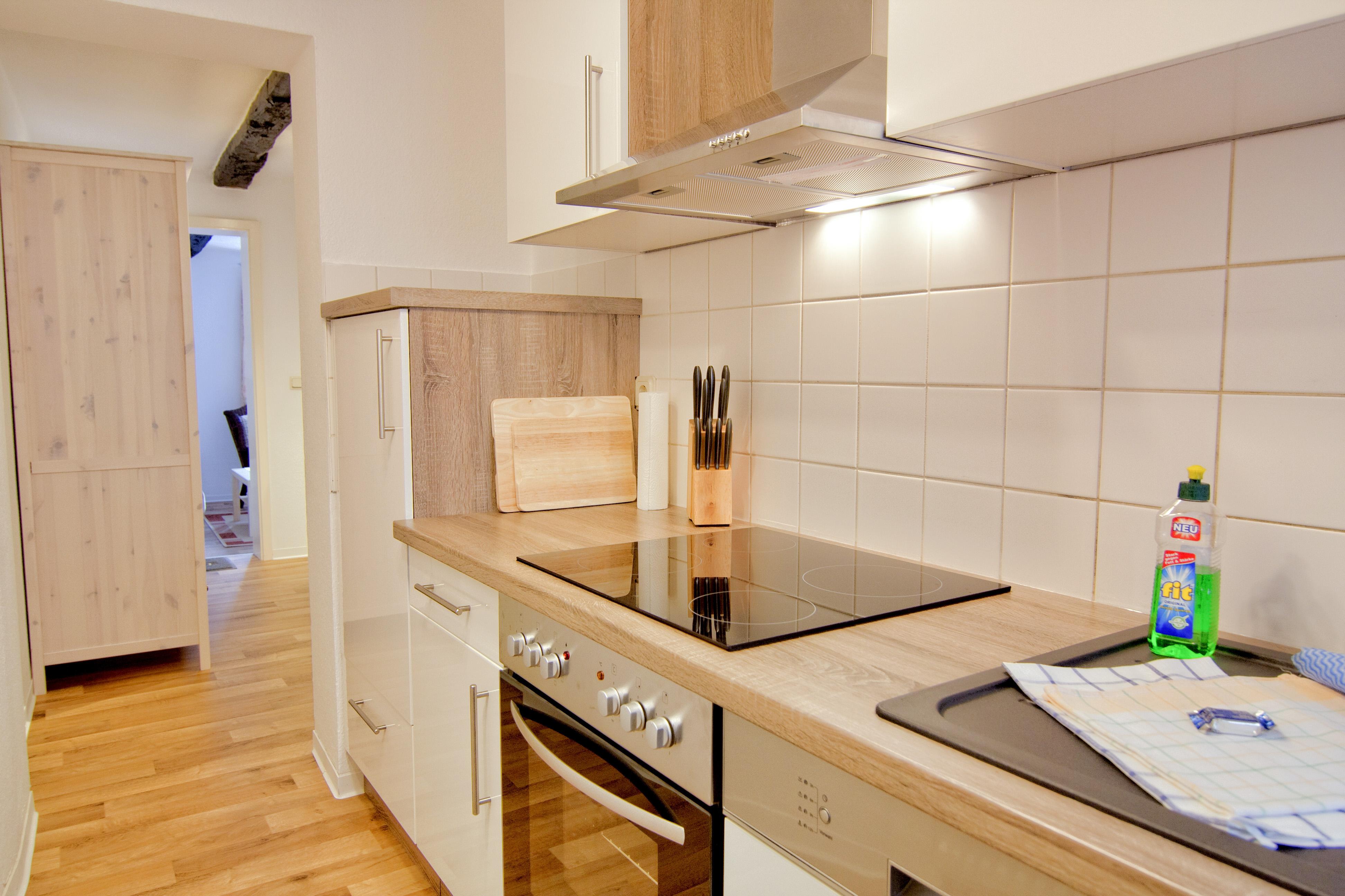 Küche mit Kühlschrank, Herd, Ceranfeld und Spüle