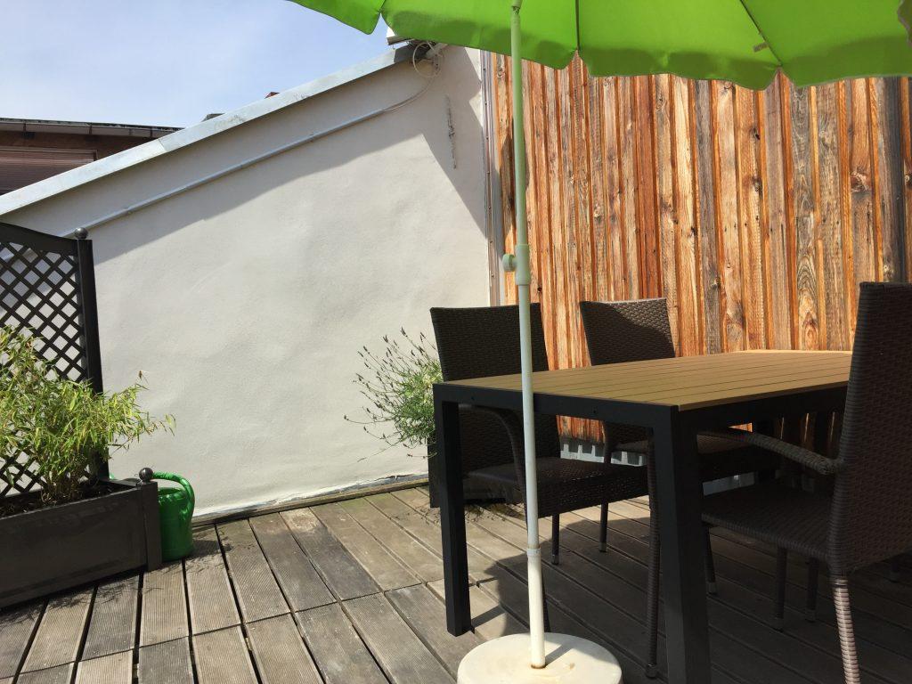 Dachterrasse mit Tisch und Stühlen, Sonnenschirm und Blumenkübeln