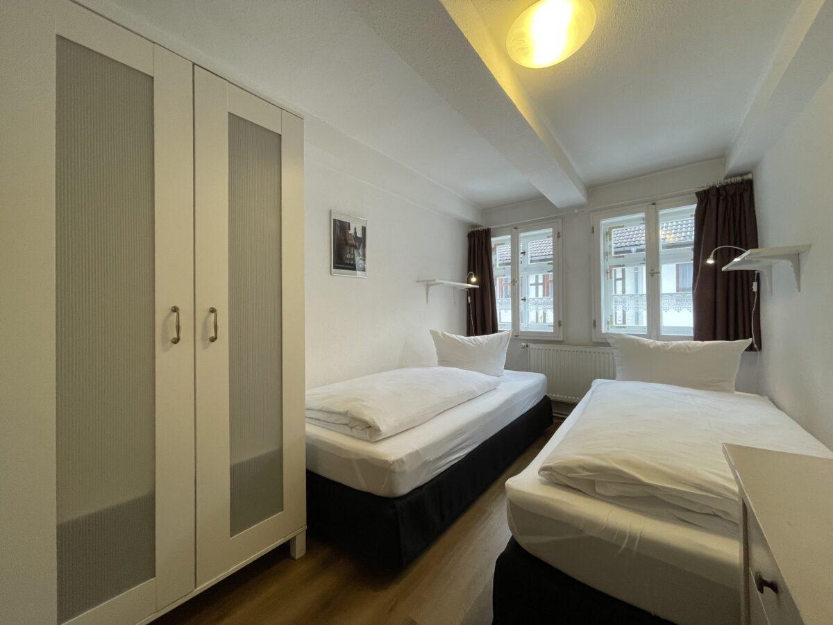 Kleines Schlafzimmer mit zwei Einzelbetten und Kleiderschrank