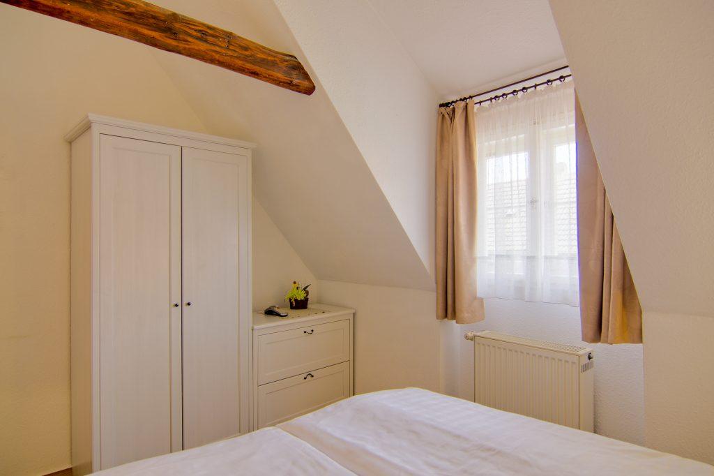 Schlafzimmer mit Fenster, Schrank und Kommode