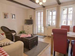 Wohnzimmer mit Sofa, Fernseher und Essecke