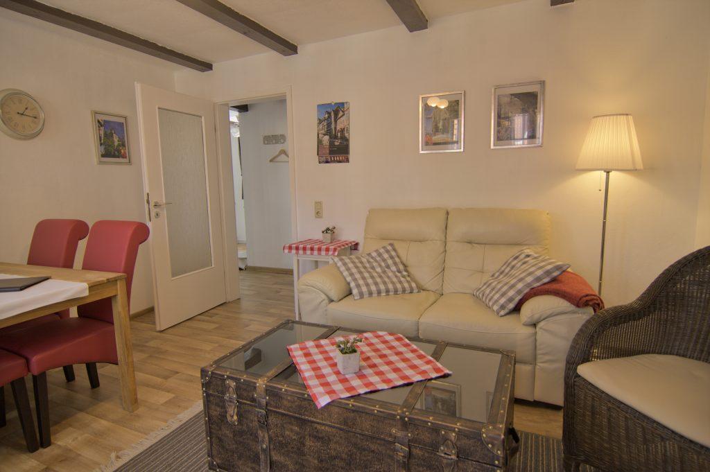 Wohnzimmer mit Sofa, Sofatisch und Sessel