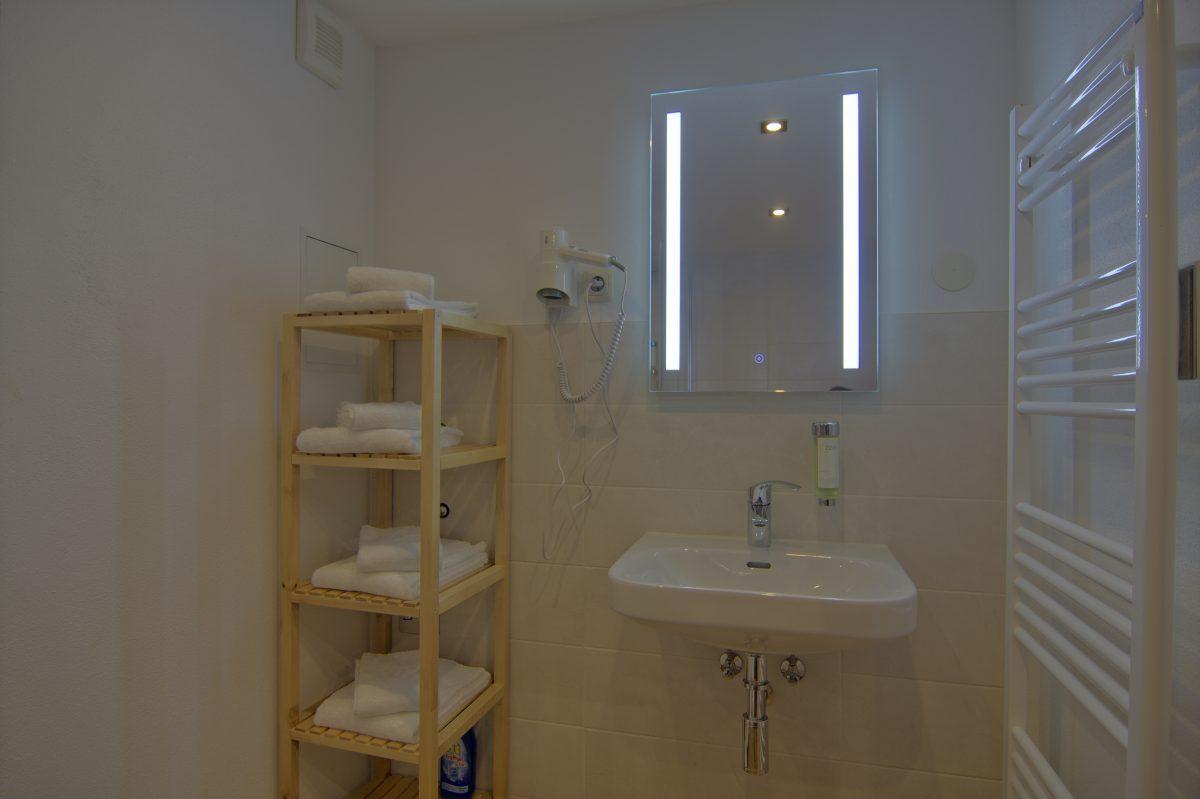 Bad mit beleuchtetem Spiegel und Fön
